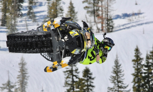 A green snowmobiler has his sled sideways in the sky.