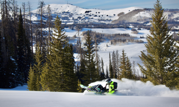 A snowmobiler rides through fresh powder at the foothills of mountains.