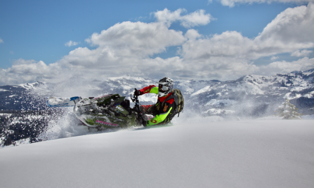 A snowmobiler banks into fresh snow while driving towards the camera.