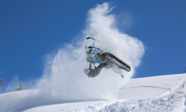 A snowmobiler gets air with a blue sky backdrop.