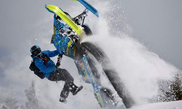 A snowmobiler rides his snowmobile upside down with only his hands on the handlebars.
