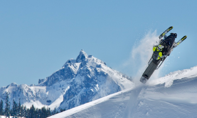 A snowmobiler is suspended in the air at the top of a mountain with more snow covered peaks in the distance.