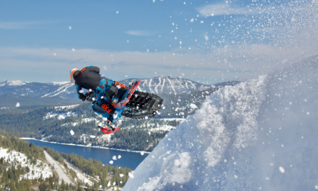 The back of a snowmobiler as he jumps off a mountain.
