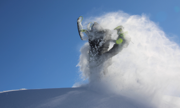 A snowmobiler does a wheelie in the midst of a cloud of snow.