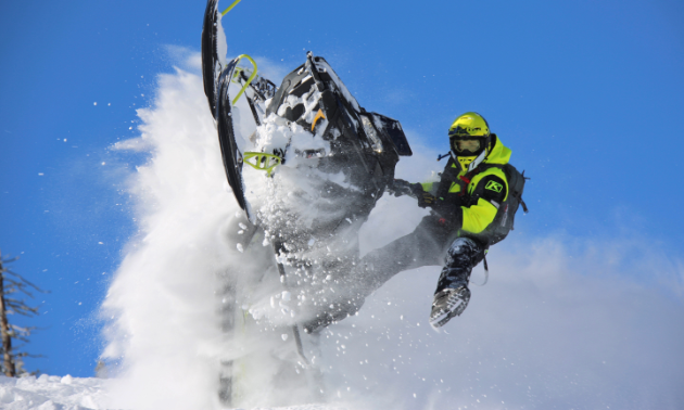 A snowmobiler gets vertical with a plume of snow all around him.