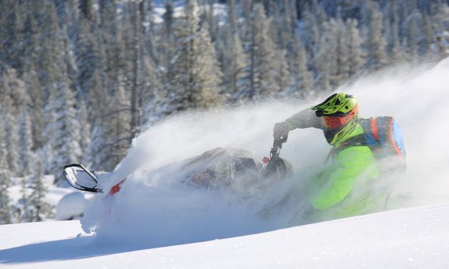 A green sledder carves through pristine snow.
