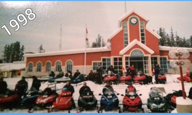 An old photo of snowmobiles parked in front of Tumbler Ridge City Hall.