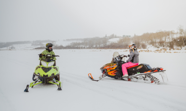 Two snowmobilers stop and visit with one another on a trail.