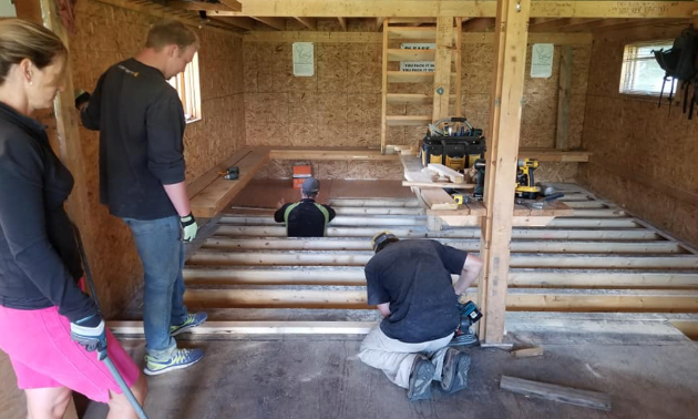 Workers are on their knees refinishing a floor in a cabin.