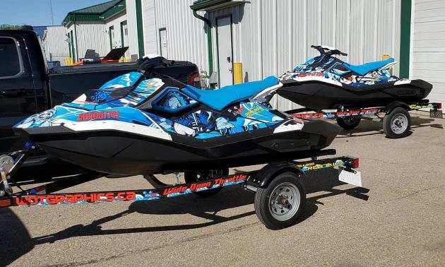 Two custom-wrapped Sea-Doos on trailers.