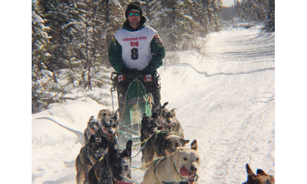 Bud Streeper races dog sleds across a snwomobile trail.