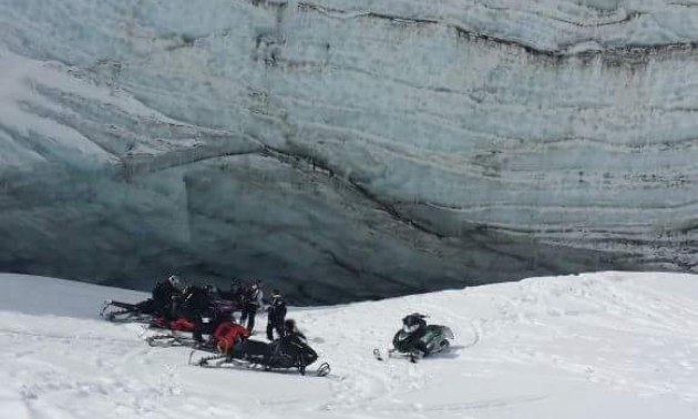 A group of snowmobilers gather under a mountain near a large snowpack.