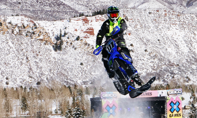 A blue snow bike gets massive air at an X-games competition.