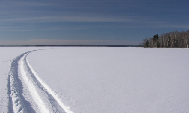 A large, open plain of snow has a single track leading through it.