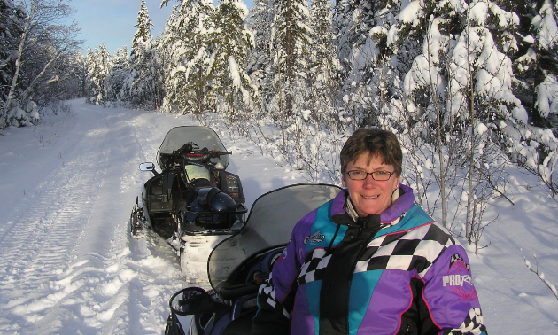 Rob Vipond's wife, Shirley, sits on a snowmobile in The Pas, Manitoba.
