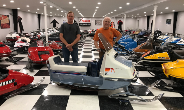 Two men stand behind a 1966 prototype Evinrude Sail Master in a room full of vintage snowmobiles