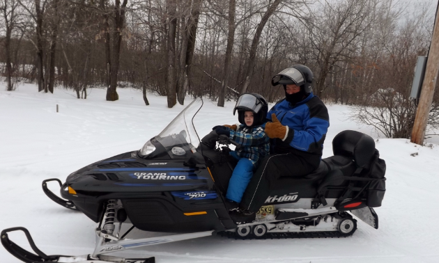 Barry Malcolm takes his grandson, Grayson, out for rides on his snowmobile.