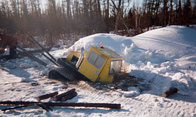 A Bombardier Bombi snow groomer is partially submerged in water.