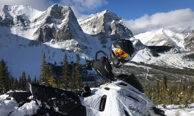 A snowmobile has a helmet on the handlebars in the foreground and towering mountain peaks in the background.