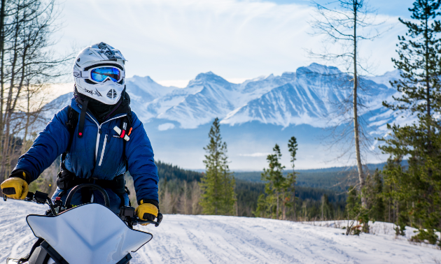 A snowmobiler looks on in the foreground with a horizon of mountain peaks in the background.