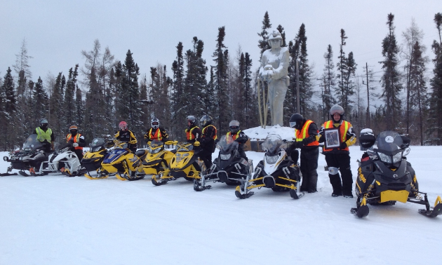 Thompson, Manitoba, where snowmobilers pose for a photo at the Journey for Sight Ride.