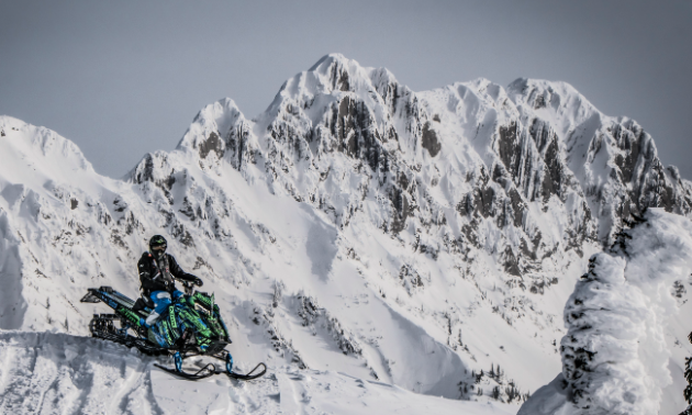 A man sits on his snowmobile amidst towering mountain peaks filled with snow.