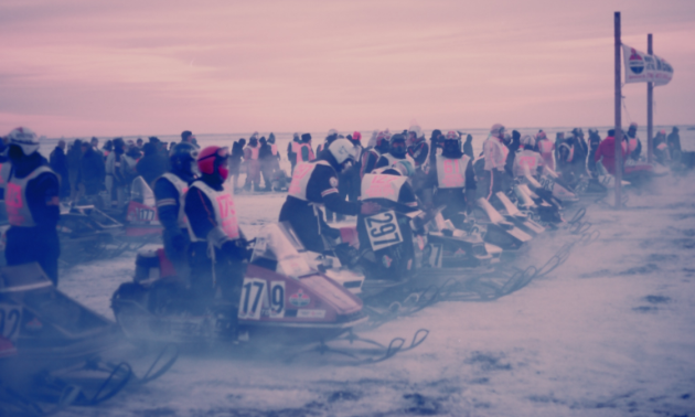 Snowmobile riders line up at a starting line in blistering cold conditions