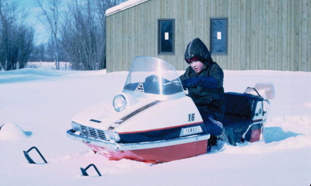 Bill Hammond's son David at 10 years old rides a snowmobile