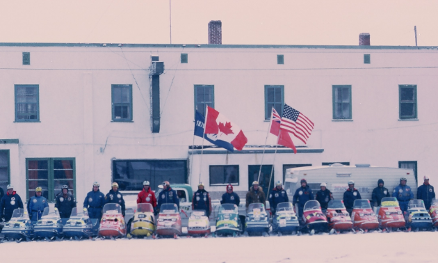 Snowmobile riders line up for the Manitoba Centennial in front of a building