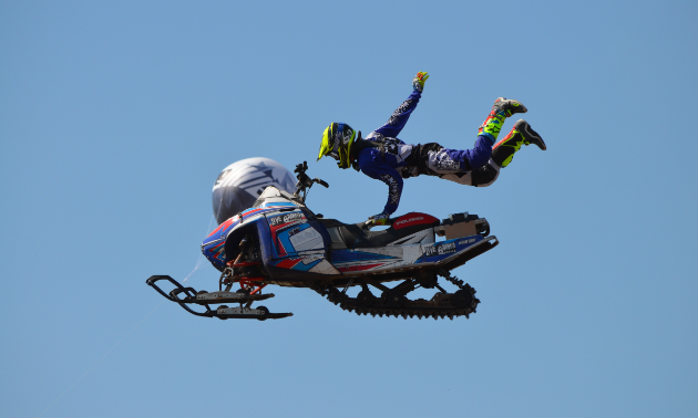 Dan Shaffer holds onto his snowmobile with one hand