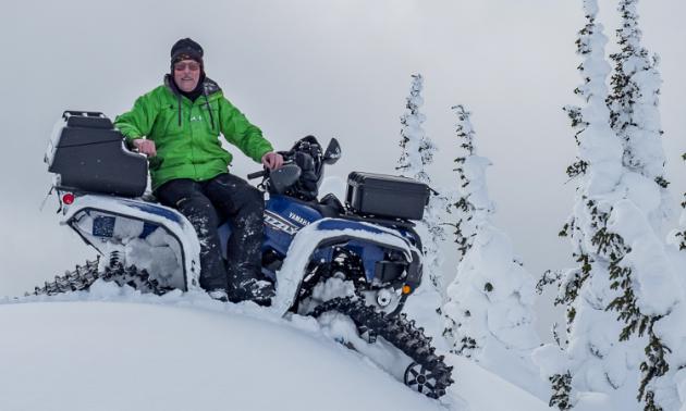 Doug Williamson sits on his ATV with tracks