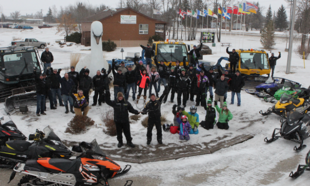 The Swan Valley Snowmobile Club is gathered to celebrate their Sledtown Showdown contest win in 2015.