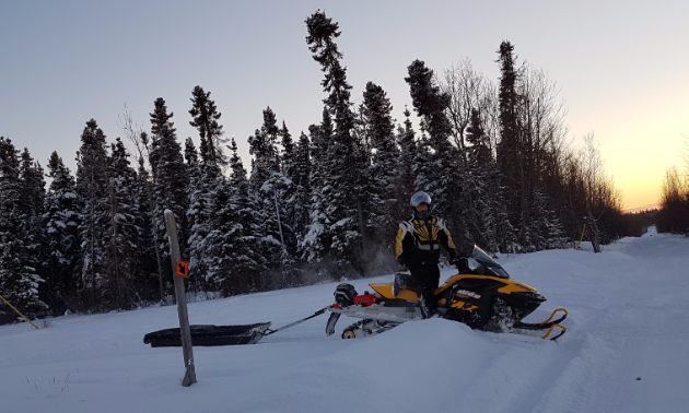 Kelly Martens poses on his snowmobile next to a trail