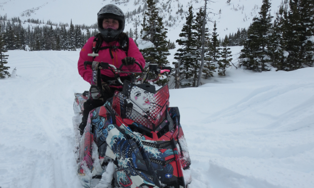 Kelsey Poelt poses on her pink snowmobile on the first day of spring.