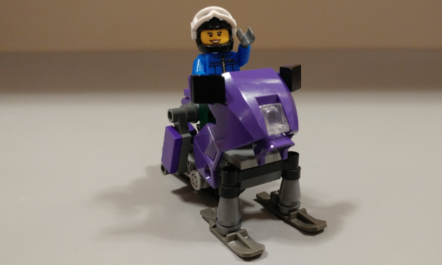 A happy sledder rides a Lego snowmobile