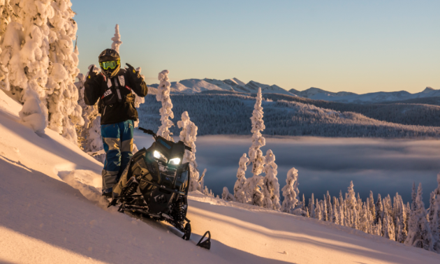 Logan Thibodeau poses with his snowmobile at sunset