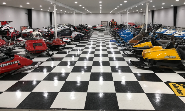 The first floor of Lorne's Vintage Sleds boasts a bunch of snowmobiles and a shiny checkered floor.