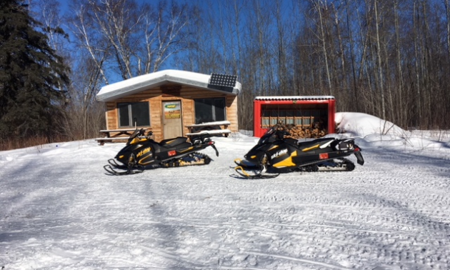 A warm-up shelter with a shed beside it and two snowmobiles parked in front in Swan River.