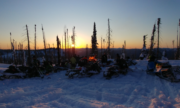 Snowmobilers gather for a bonfire at sunset