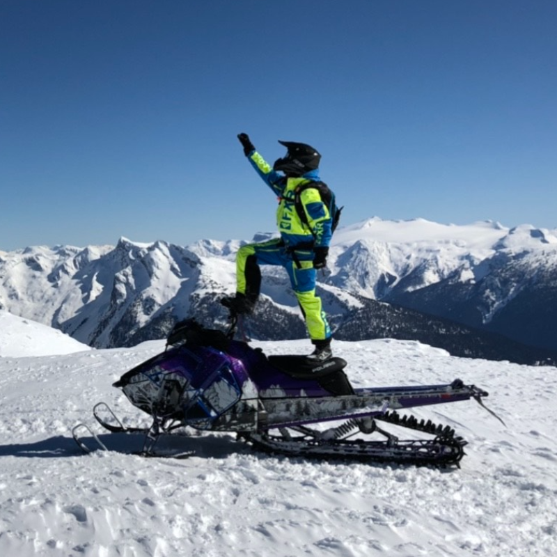 Andrew McKenzie stands on top of his black snowmobile, holding up his hand with a skyline of mountains in the distance.