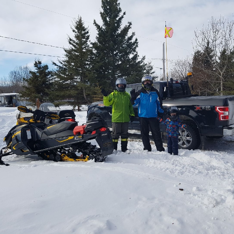 Audun Klath stands next to his father, son and a truck and two snowmobiles.