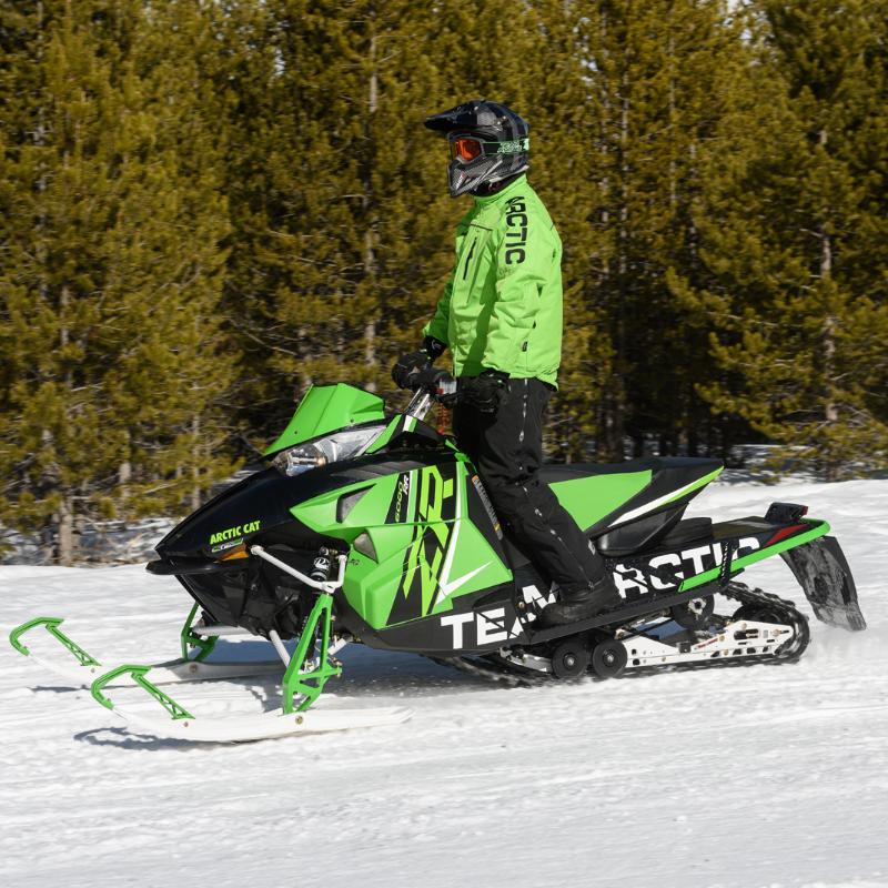 A snowmobiler wears green on a green Arctic Cat snowmobile.