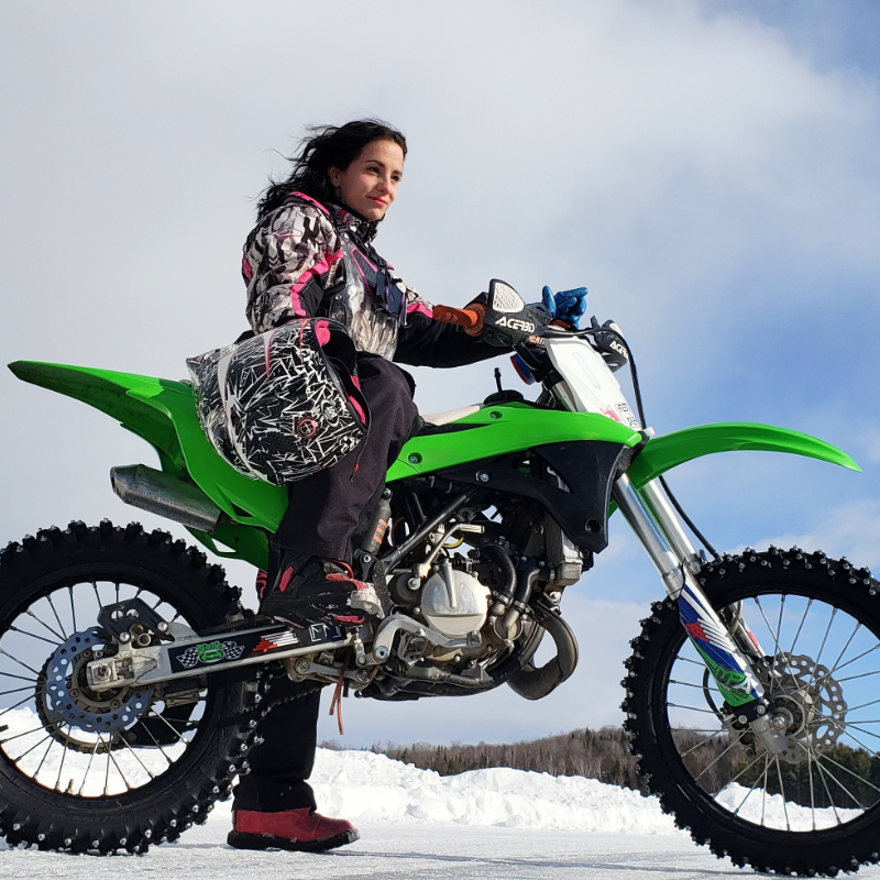 Jessica Rainville poses on a green dirt bike with clouds and mountains in the distance.