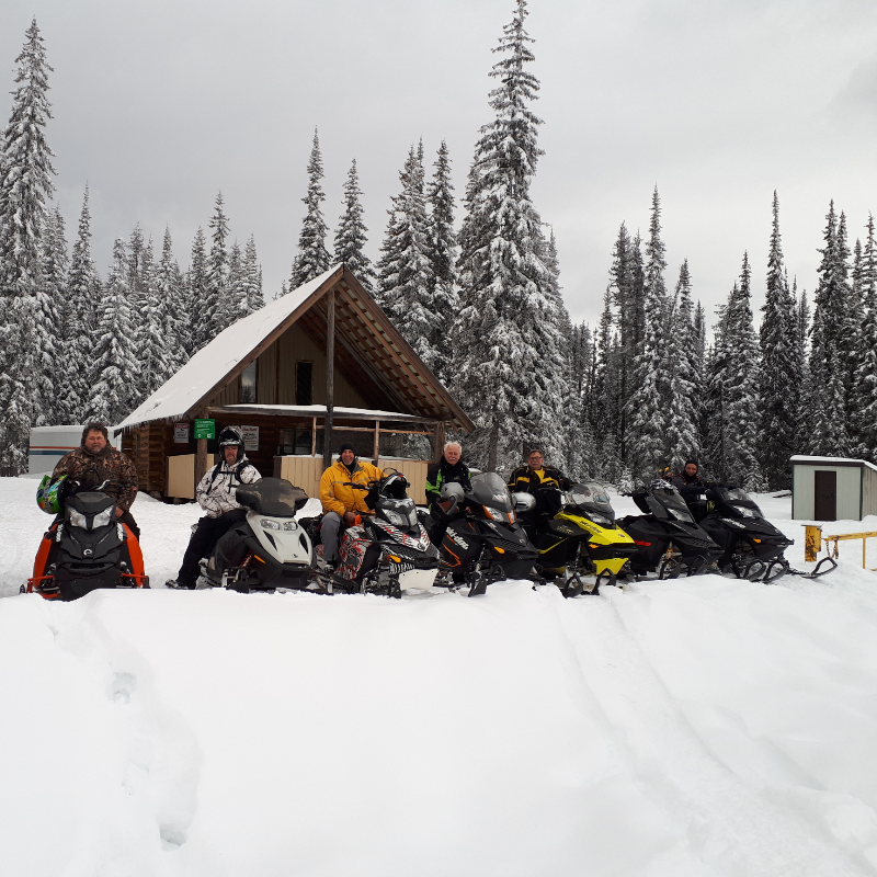 A row of snowmobilers line up in front of a tall cabin with a steep roof amidst the forest.