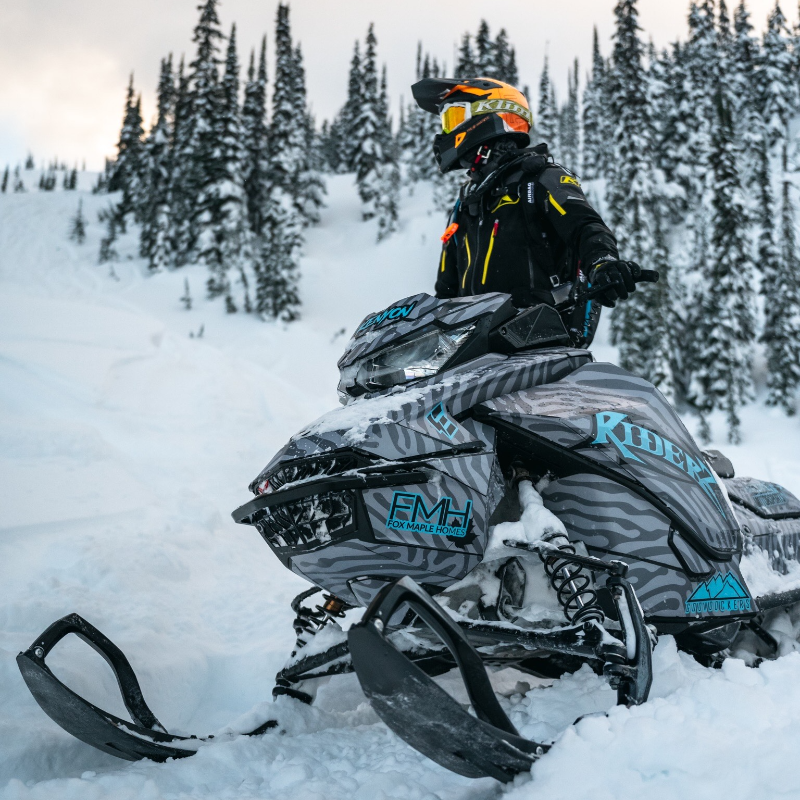 Mason Kenyon sits on a blue and black snowmobile wearing an orange helmet and orange goggles.