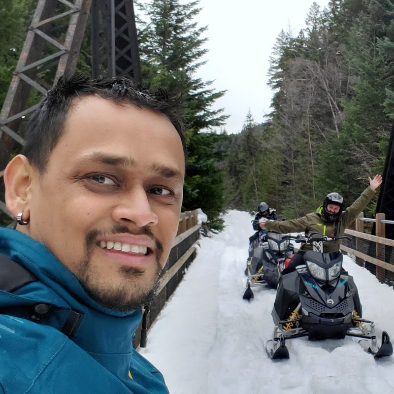 Melvin Garib smiles for the picture on a snowmobile trail going over a bridge with a snowmobiler behind him waving.