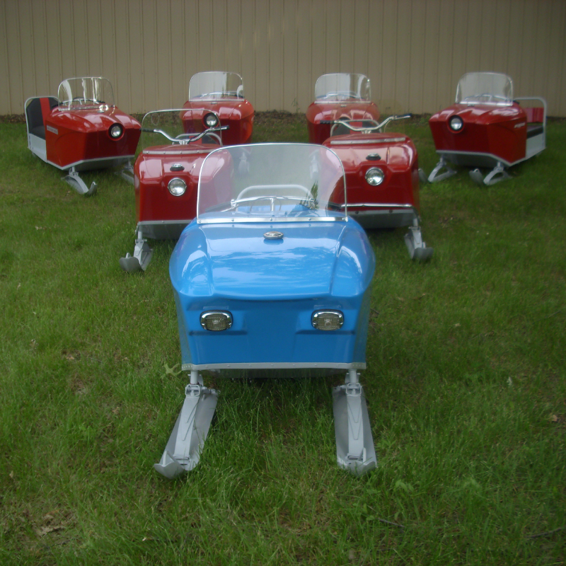 A blue Sno Scoot in front of six red Sno Scoot snowmobiles.