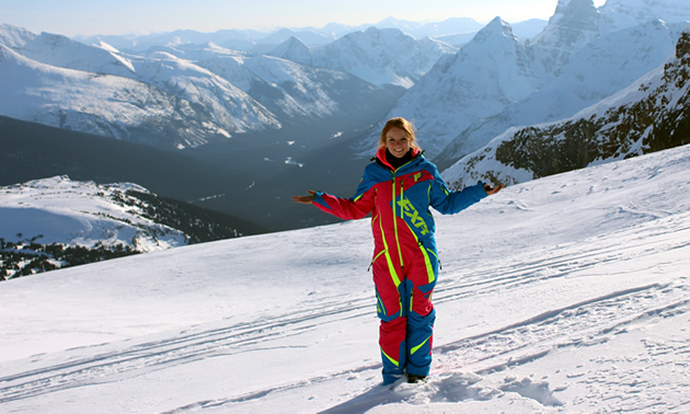 A young woman stands at the top of the mountains.
