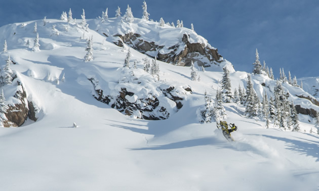 A guy in the distance on a snowmobile sledding on a large snow-covered pristine mountain.