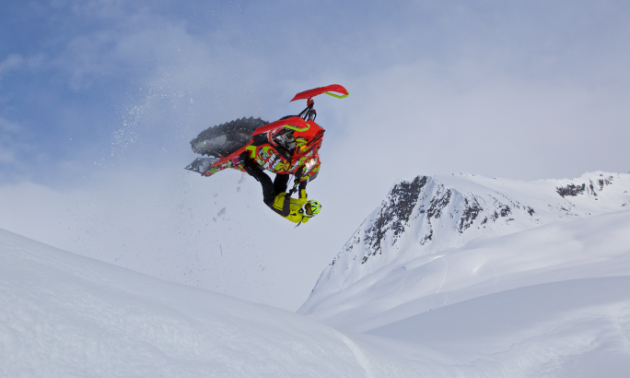 Ashley Chaffin is upside down in the air, doing a backflip on her snowmobile.